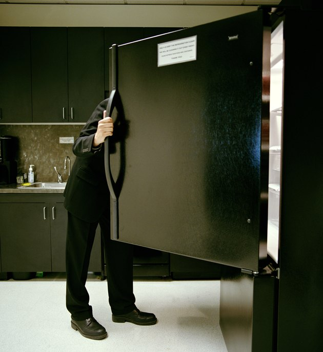 Mature businessman looking in refrigerator in office kitchen