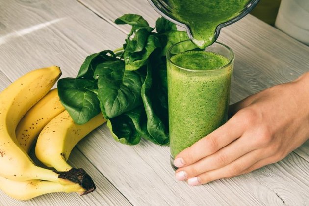 Female hand pours a smoothie of banana and spinach in glass on a wooden background