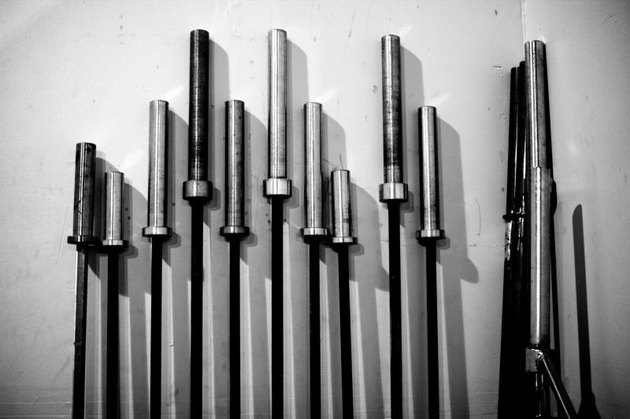 Weight lifting barbells leaning against a wall taken in black and white.