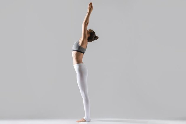 Young attractive woman practicing yoga, standing in mountain exercise, Tadasana pose, working out wearing sportswear, white pants, top, indoor full length, isolated, grey studio background