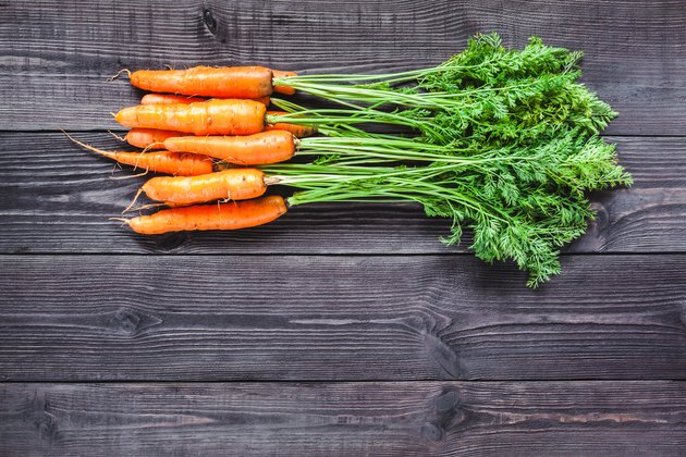 Ripe fresh carrots on a wooden background.