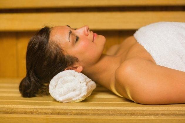 Peaceful brunette relaxing in a sauna