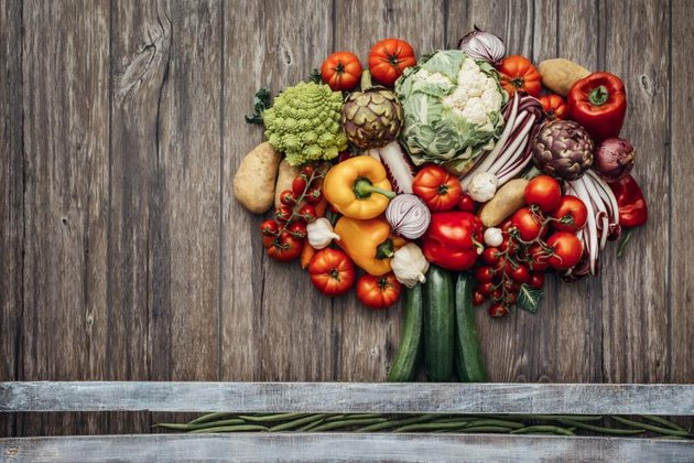 Colorful lush tree made of freshly harvested organic vegetables on a rustic wooden table, nutrition and nature concept