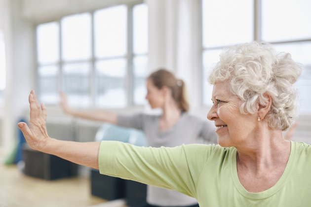 Senior woman doing stretching exercise at yoga class