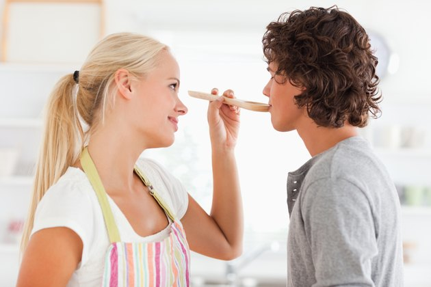 Blonde woman making her fiance tasting her meal