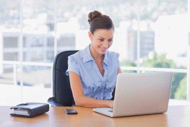 Happy businesswoman working on her laptop