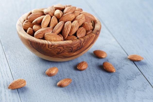 roasted almonds in bowl on blue wooden table