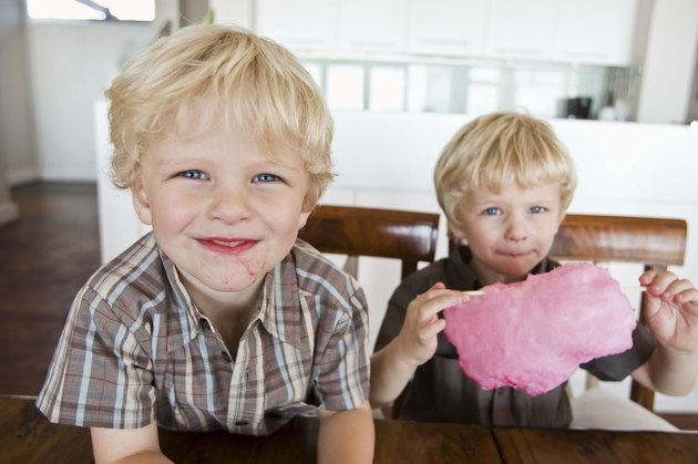 Twin boys sharing cotton candy