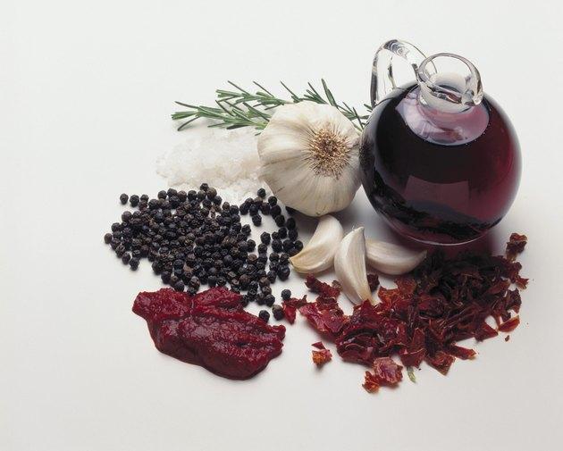 Glass jug of balsamic vinegar with assorted edible flavorings