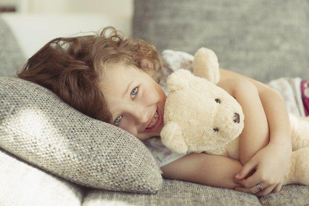 Young girl embracing teddy bear on sofa