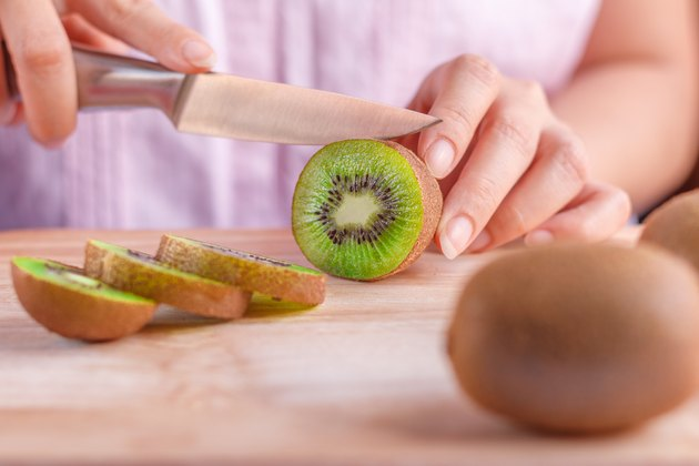 Woman food preparation - cutting a kiwi fruit.