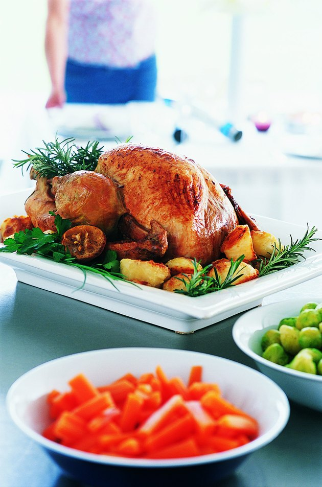 Roast Turkey and Vegetables with a Woman in the Background