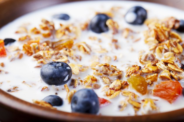 Healthy breakfast. Fresh granola, muesli with berries, honey and milk