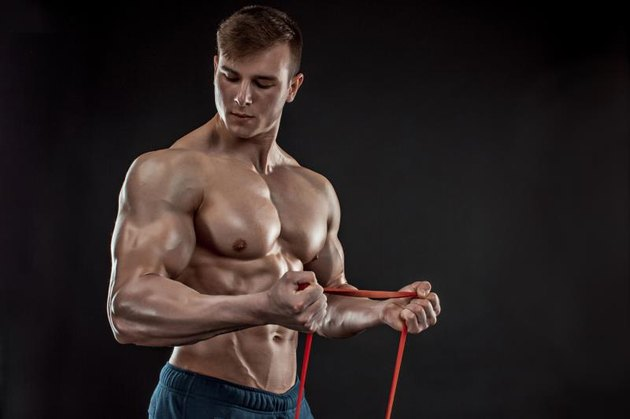 A young athletic man exercising and with a chest expander,  or resistance band.