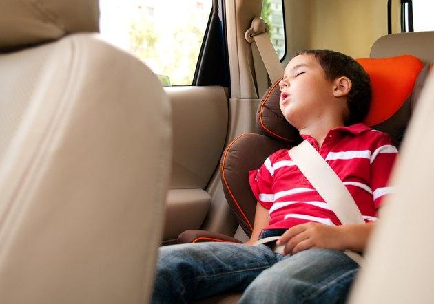 Litle boy sleeps in safe chair car
