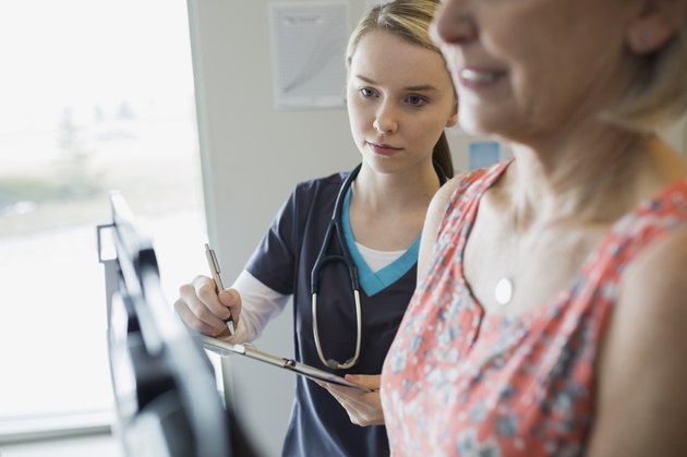 Nurse noting patients weight on scale in clinic