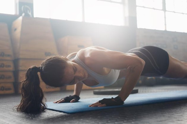 Shot of young woman doing push-ups at the gym. Strong female athlete doing pushups on exercise mat at gym. Female exercising on fitness mat at gym.