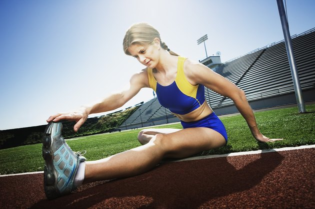 Athletic woman stretching on field
