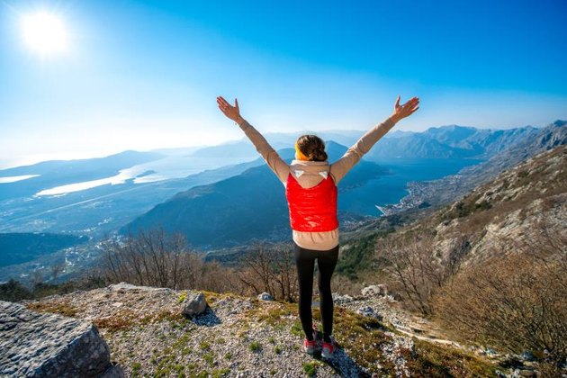 Sport woman in red vest standing on the top of mountain