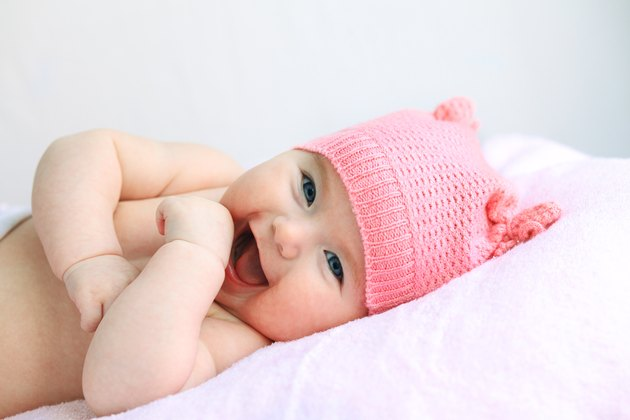laughing baby girl in pink hat