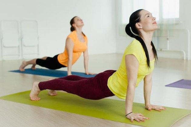 two women practicing the Bhujangasana (Cobra Pose) in yoga studio