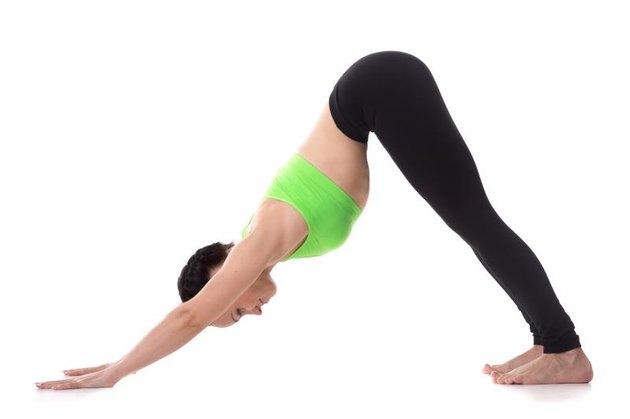 Sporty girl on white background stretching in downward-facing dog yoga pose, adho mukha svanasana, asana from Surya Namaskar sequence, Sun Salutation complex