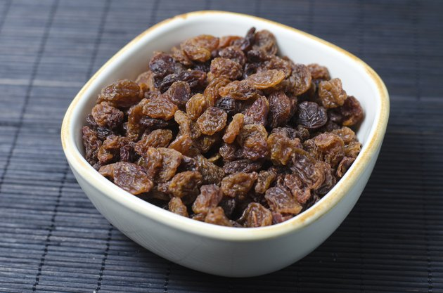 Bowl of raisins on dark background