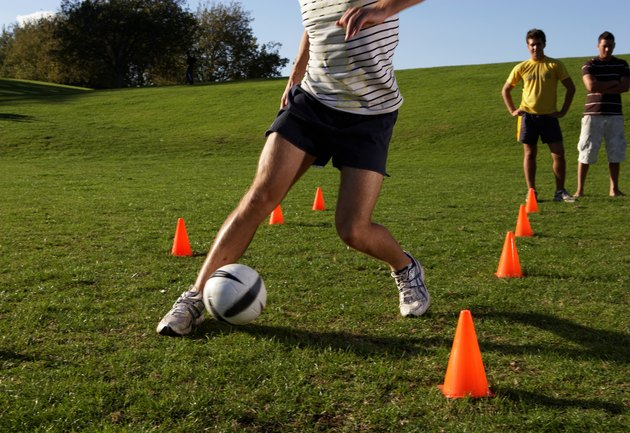Men practising football, dribbling through cones in field