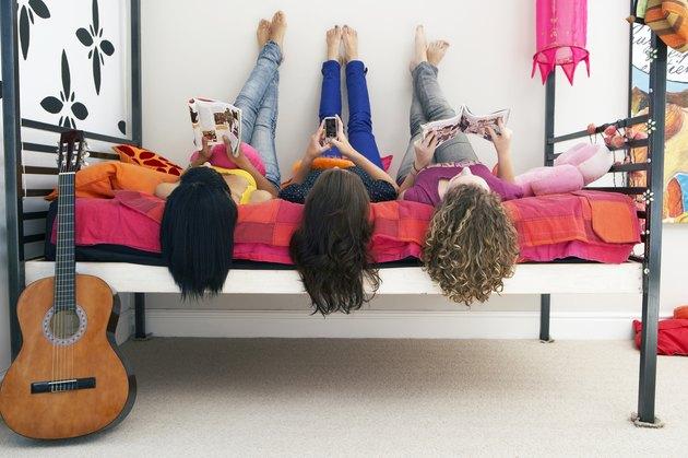 three girls lying on bed
