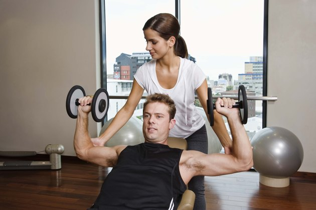 Woman assisting man with weightlifting at gym