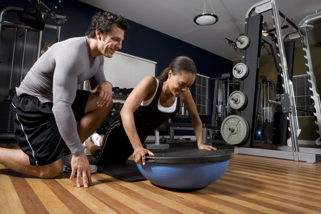 Trainer instructing a young woman on a fitness ball in the gym