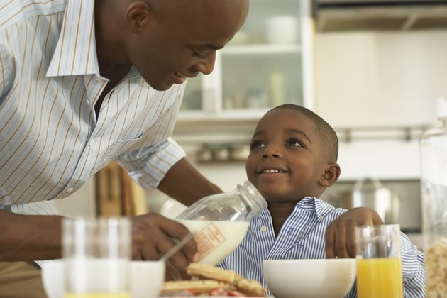 Father pouring milk in bowl for son (5-7) at breakfast table, smiling