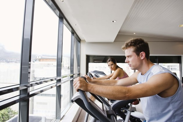Man and woman on exercise bikes at gym