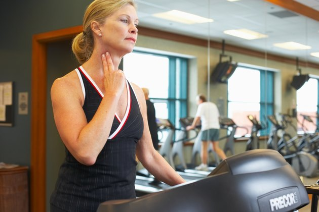 Woman checking her pulse on treadmill at gym