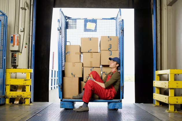 Worker sitting on loading dock with boxes
