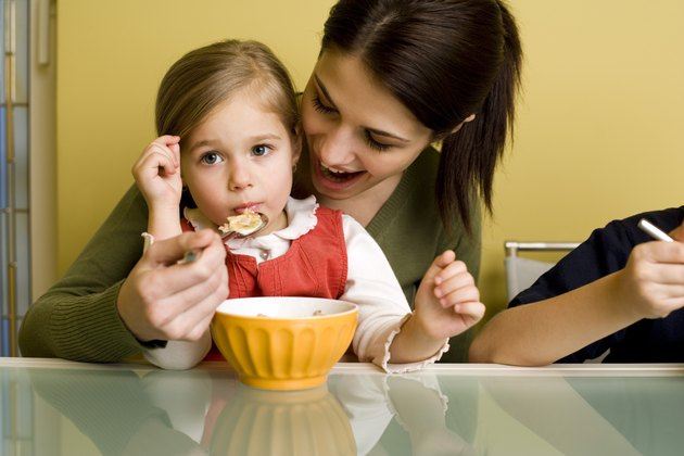 Woman feeding girl cereal