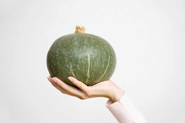 Person holding a kabocha pumpkin