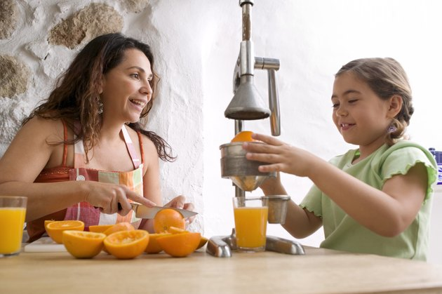 Mother and daughter squeezing oranges for juice