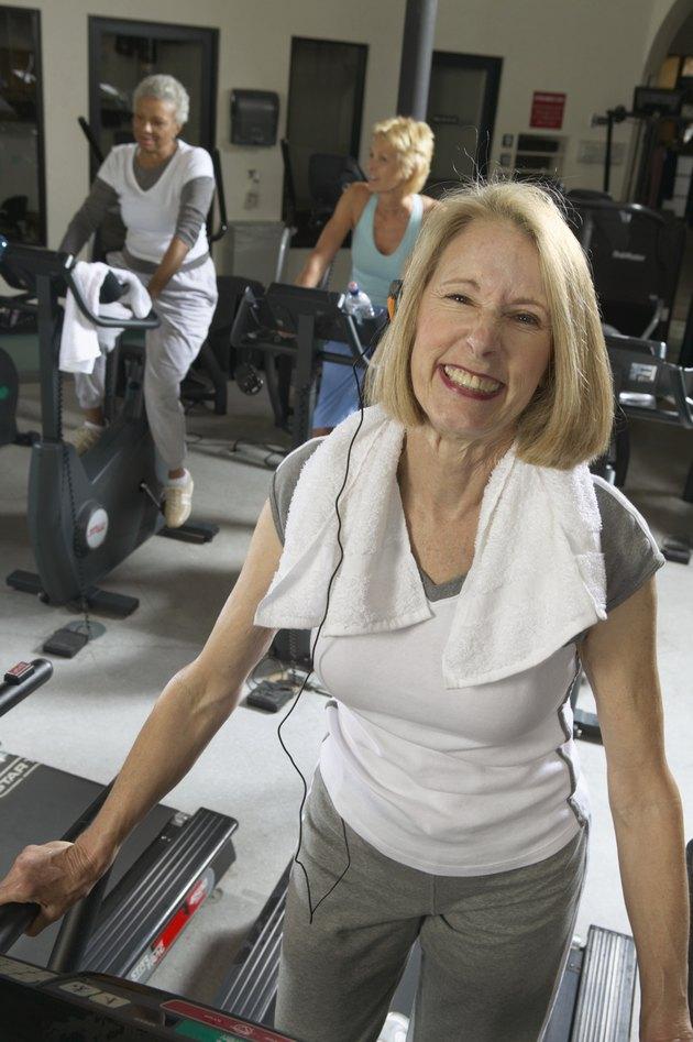 Senior woman wearing earphone on machine in gym, smiling, portrait