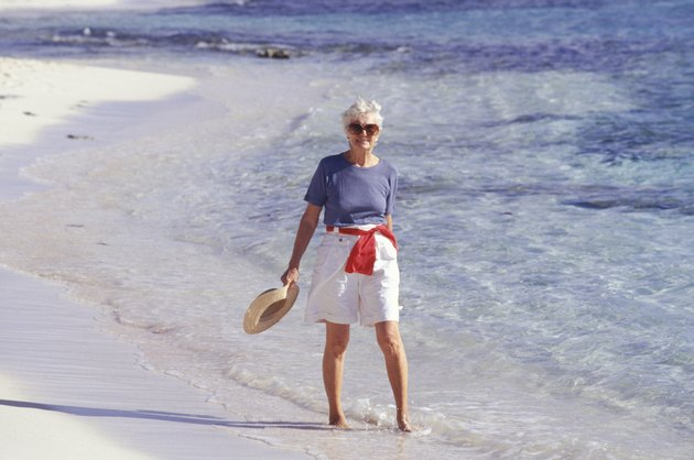 Senior woman walking barefoot on beach