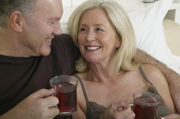 Mature couple holding cups of tea in bed, smiling, close-up