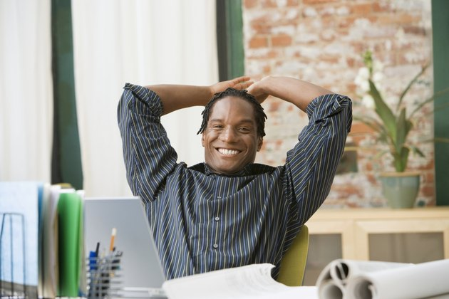 African businessman with hands behind head