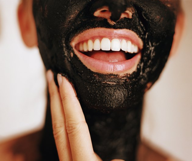 Woman with mud mask on face and neck, mouth open
