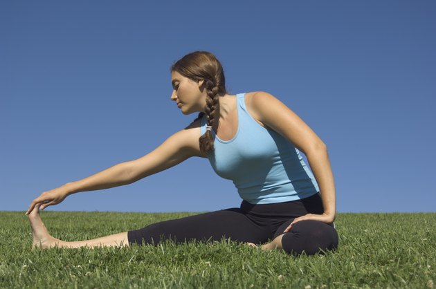 Young woman stretching in field