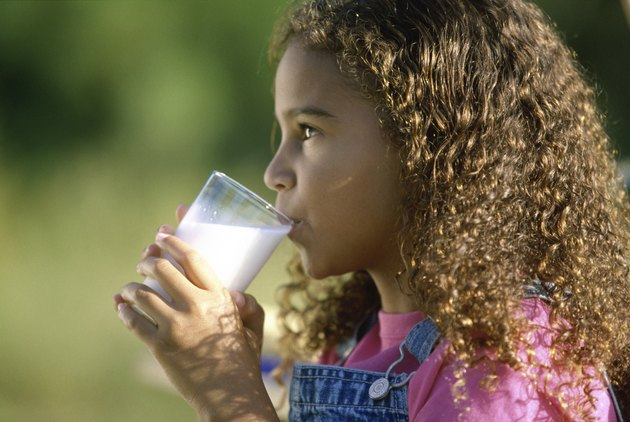 Side profile of a girl holding a glass of milk