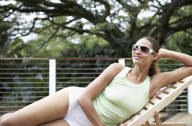 Mixed Race woman relaxing in lounge chair