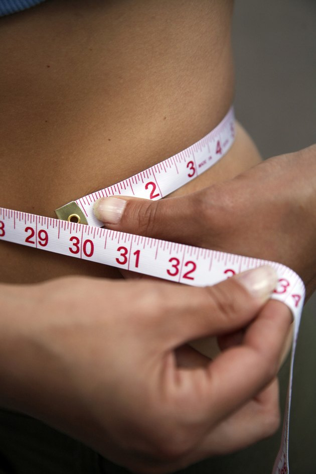 Mid section view of a woman measuring her waist with a tape measure