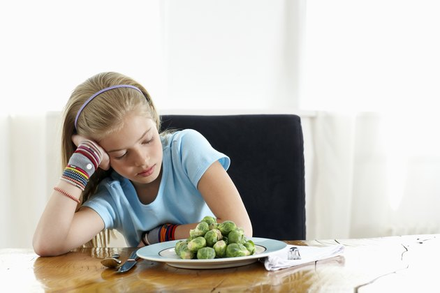Girl (9-11) sitting at plate of sprouts