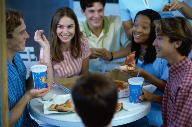 High angle view of a group of teenagers eating pizza in a restaurant