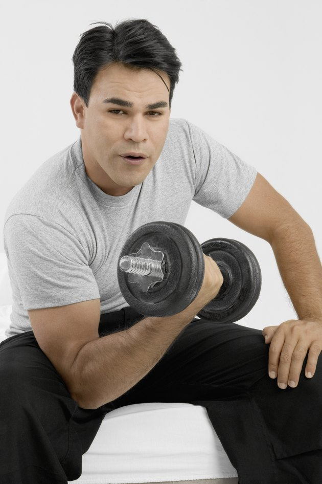 Man sitting and holding dumbbell